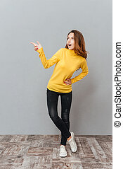 Excited young woman in yellow sweater standing and pointing away