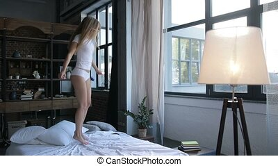 Excited young woman jumping on bed at home