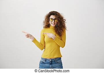 Excited young woman pointing her finger towards blank space isolated over grey background.