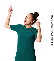Excited young woman pointing up and laughing