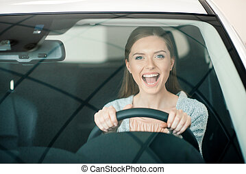 excited young woman sitting in new car and looking at camera