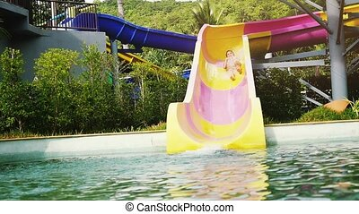 Excited young woman sliding down the fast water slide in fun...