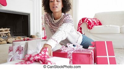 Excited young woman unwrapping her Christmas gifts sitting...