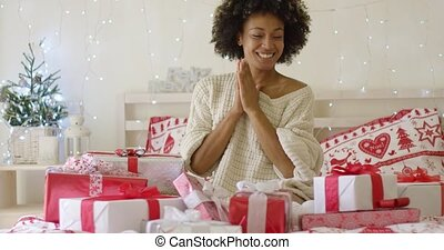 Excited young woman with a pile of Xmas gifts