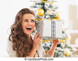 Excited young woman with christmas present box in front of christmas tree