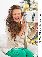 Excited young woman with christmas shaking present box in front of christmas tree