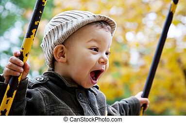excitement and freedom - excited toddler on a swing...