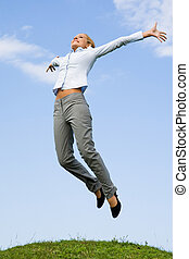 Excitement - Portrait of happy female jumping over green...