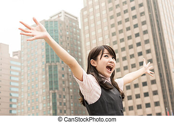 Exciting business woman raised hand in outside of city.