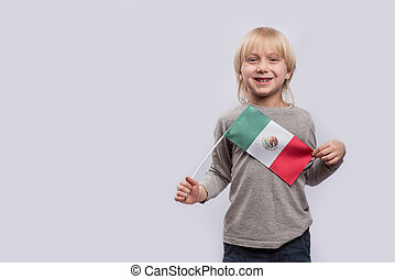 Exciting Fair-haired boy holding flag of Mexico on white background