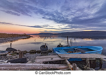 exciting landscape on a lake with wooden pier and boat .
