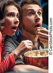 Exciting movie. Close-up of shocked young couple eating popcorn and drinking soda while watching movie at the cinema
