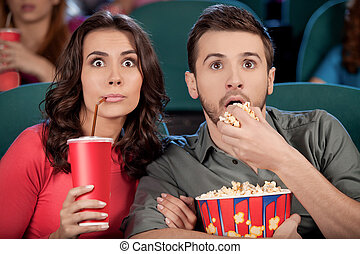 Exciting movie. Shocked young couple eating popcorn and drinking soda while watching movie at the cinema