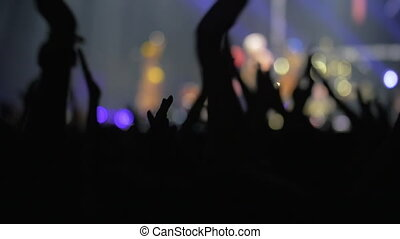 Slow motion defocused shot of people getting excited with concert. Silhouettes of applauding hands in foreground and singer on stage in background
