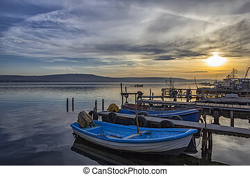 exciting sunset on harbor with boats