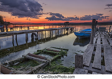 Exciting sunset on the harbor with wooden piers and boat. Horizontal view