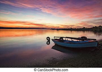 exciting sunset / sunrise on a seashore with boat