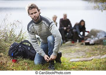 excursionismo, macho, atar, cordón, con, amigos, en, plano de fondo