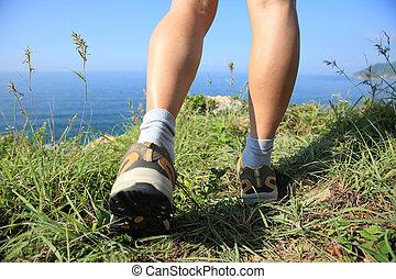 excursionismo, piernas, ambulante, en, playa, pico de la montaña