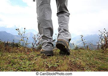 excursionismo, piernas, en, pico de la montaña