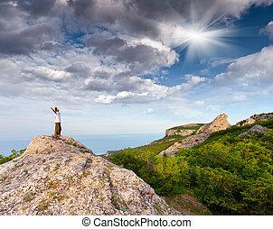 excursionista, en la cima de, un, roca, con, el suyo, manos arriba, gozar, día soleado