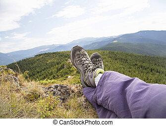excursionista, piernas, y, botas, vista, en, el, pico de la montaña, relajante