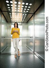 executiva, usando, smartphone, em, elevador
