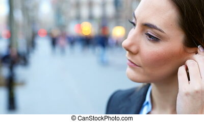 Executive asking phone call putting witeless earbuds in the street at evening