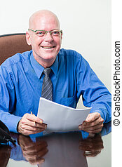 Executive at desk holding papers