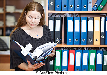 Executive business woman looking at documents in folder at office