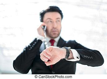 Executive businessman looking at a wristwatch.