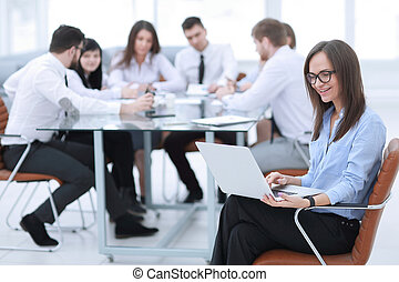 Executive businesswoman with laptop on blurred background business team