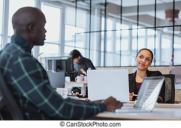 Young woman looking at male colleague while sitting at a table with laptop. African executive discussing work with coworker.