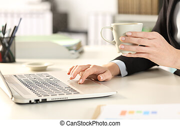 Executive hand using laptop holding a cup of coffee