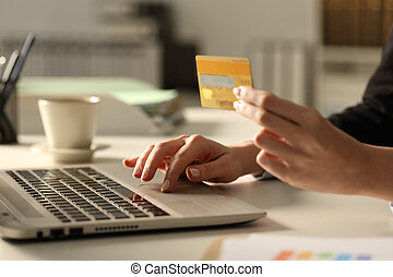 Executive hands with credit card an laptop paying at night