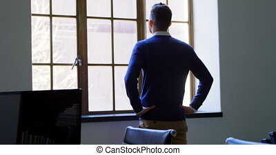 Executive looking through window in office 4k - Rear view of...