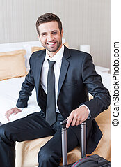 Executive on the Go. Confident young businessman in formalwear carrying suitcase and smiling while sitting on the bed in hotel room