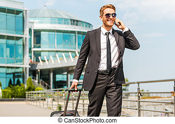 Executive on the Go. Handsome young businessman in full suit carrying suitcase and talking on the mobile phone while walking outdoors