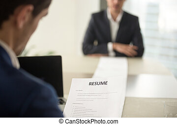 Executive reading cv during job interview, focus on resume, clos