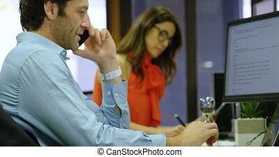 Executive talking on mobile phone while using laptop 4k