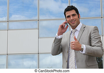 Executive using a cellphone outside and giving the thumbs up