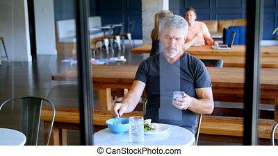Executive using mobile phone while having food 4k