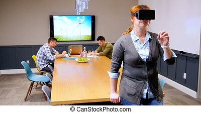 Executive using virtual reality headset while colleagues working in background 4k