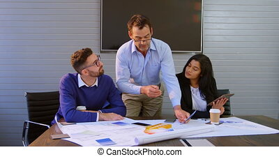 Executives discussing over blueprint in conference room 4k -...