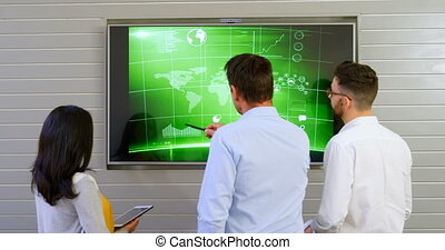 Executives discussing over lcd screen in office 4k - Rear...