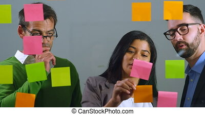 Executives discussing over sticky note on glass wall 4k -...