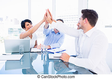 Executives giving high five in a business meeting - Smartly...