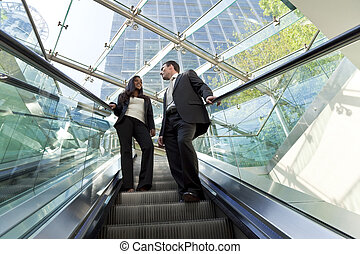 Executives on an Escalator - A young male and female ...