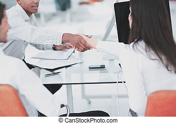 executives shaking hands after a business meeting in the office
