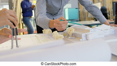 Executives working on blueprint and architectural model 4k